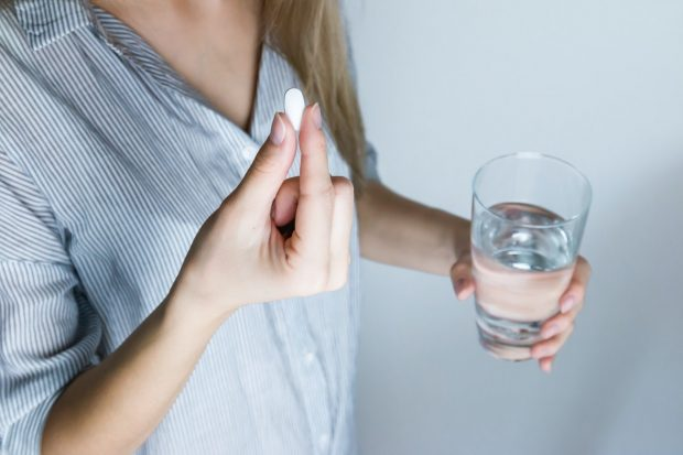 girl holding a pill and a glass of water